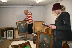 Jesse Sipola (oik.) ja Eero Yli-Vakkuri käyttävät nykytaideteoksessaan muun muassa entisten rehtoreiden muotokuvia ja muuta tähän tarkoitukseen säästettyä taidetta ja opetusvälineistöä.