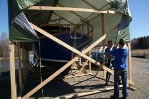 Jouko Kielo (tak.) autteli huhtikuussa poikaansa Timo Kieloa veneen keväthuoltotöissä Satamaan pystytetyn pressukatoksen suojissa.