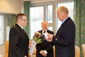 Kylmäkosken vankilan johtaja Harri Rämö muisti Erkki Saloa Kylmäkosken vankilan mukilla. Salo on neljäs mukin saanut siviilihenkilö. Myös pääjohtaja Vesterbacka sai muistoksi vankilamukin.