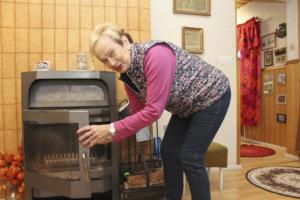 Arja Raiski lämmitti sähkökatkojen aikana taloaan takalla.