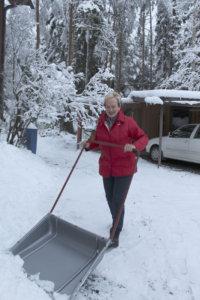Arja Raiski pitää pihan puhtaana kolaamalla. Viikonloppuna runsas lumentulo tiesi tuntien lumitöitä.