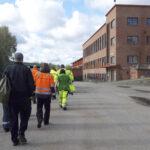 Avustajajoukko siirtyi ruokatauolta kohti tehdasalueen portilla tehtäviä kuvauksia. Kuva: Mikko Peltoniemi